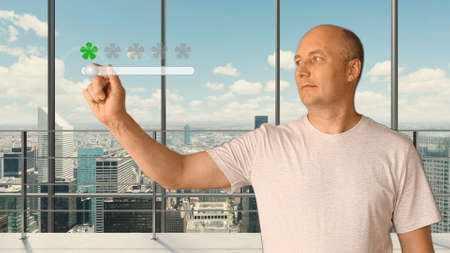 A man standing in a modern office with panoramic windows sets a rating on a virtual screen. Service rating 5 stars. Future technologies. City skyline outside the window. Stockfoto