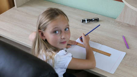 Little girl draw line by pencil with ruler in notebook. Back to school concept. Young girl sitting by table indoors. Light wood table white caucasian girl. Pen glasses laying on table.