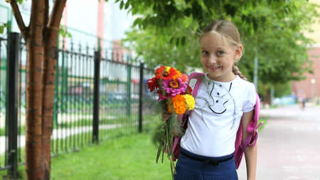 Young pretty girl standing near school with backpack and flowers sunny day. Back to school. Schoolgirl go to study. Girl smelling flowers and laughs. Primary school student outdoors. Windy day. Archivio Fotografico