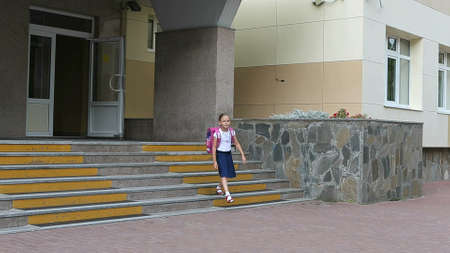 Young girl with backpack go out from school downstairs. A girl in school uniform comes out of the school and descends the stairs from the porch. White blouse dark blue skirt purple backpack. Handheld. Archivio Fotografico