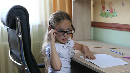 Young caucasian girl in glasses sitting on chair by table. Indoors close up view on pretty girl in glasses. White caucasian girl wrote down by pen on paper. Back to school concept close up shot.