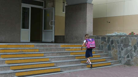 Young girl go to school walking by staircase come in to school entrance. Back to school concept. 1 september girl with backpack go upstairs to school door. Handheld camera shot summer autumn day.