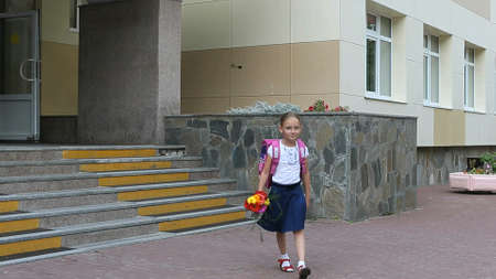 Girl walking down stairs with backpack and flowers bouquet from school door. Back to school concept. summer day hanheld shot. Girl with a bouquet of flowers walking on the background of the school.