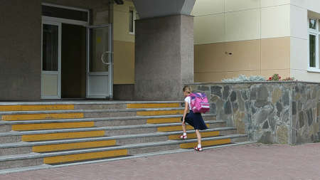 Angry girls go to school upstairs with backpack. Back to school concept. Funny shot of young caucasian girl backpack walking by staircase stopping and standing. Serious face angry girl schoolgirl. Stockfoto