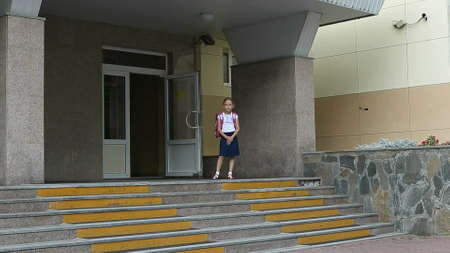 Angry girls go to school upstairs with backpack. Back to school concept. Funny shot of young caucasian girl backpack walking by staircase stopping and standing. Serious face angry girl schoolgirl. Archivio Fotografico