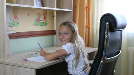 Left-handed girl sitting on chair by desk table and writing by pen in paper notebook. Back to school. Young caucasian girl smiling. Sit by table. Write by pen. White girl schoolgirl make home work.