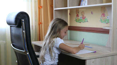 Girl sitting on black leather chair by table write something in notebook by pen.
