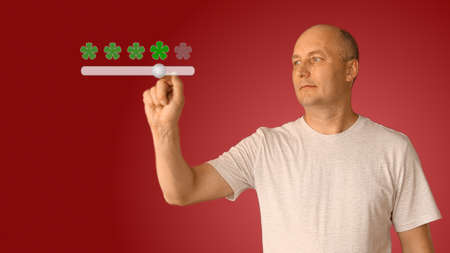 Feedback five stars from man on virtual screen. Young man move slider to set rating of services from one to five star. Creative concept flowers instead star. Caucasian man smiling and show thumbs up.