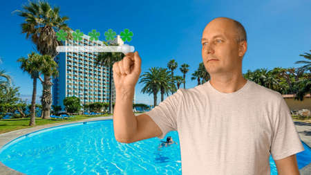 The adult man on a background of a swimming pool puts a rating of services. A rating of places for carrying out of holiday and summer rest. Excellent choice of 5 stars. Virtual screen with a slider. Stockfoto