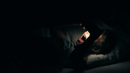 Young girl watching video on smartphone lying down in bed. Night shot in bedroom with white girl using cell phone for watching movie or video channel from internet. 写真素材