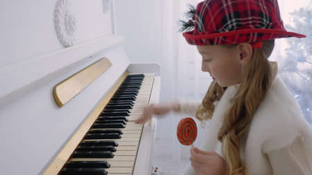 Funny girl in red hat playing music on piano and holding lollipop in hand. Cheerful girl teenager learning to play music on piano. Smiling girl playing Christmas melody