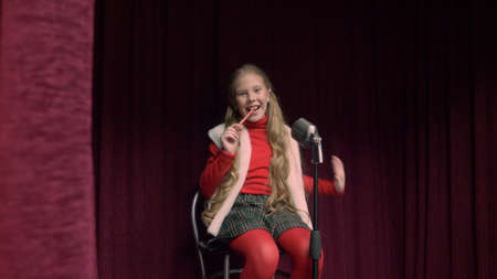 Girl with lollipop on the stage. Happy teenage girl sitting on the stage with microphone, singing and eating a lollipop.