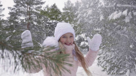 Beautiful teenager girl rejoicing winter snowfall in snowy forest slow motion. Happy young girl enjoying snowfall while walking in winter forest at frosty day