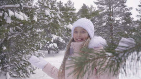 Smiling girl enjoying winter snowfall in snowy forest slow motion. Happy girl teenager while snowfall in winter forest. Snowy winter weather. Positive emotion. Winter people slowmo. Archivio Fotografico