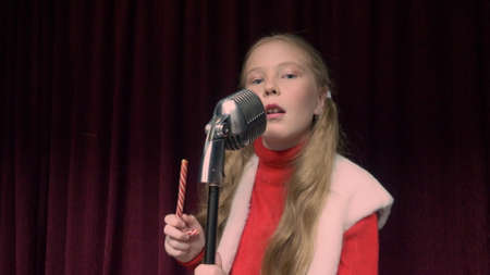 Girl singer singing song front retro microphone on dark stage while performance. Young girl singer performing and singing song dark stage. Musical Christmas show. Dark red background stage
