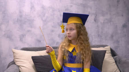 Magic astronomer in academic cap with magic wand showing on something in empty copyspace. Stargazer girl doing witchcraft with magic stick. Astronomer predicts future by stars