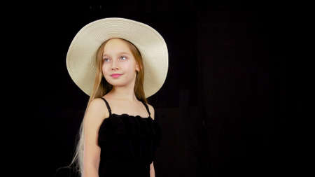 Young girl in black dress and white hat. Close up view, beautiful young model posing in evening dress and a hat, looking sidewards.