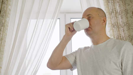 Adult man drinking morning coffee on cozy kitchen on window background. Portrait cheerful man enjoying hot tea from cup on home kitchen