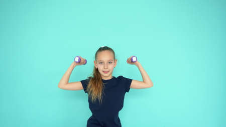 Young teenager girl lifting dumbbell at gym training on empty copyspace background. Sporty girl doing fitness exercise with dumbbell. Sport lifestyle concept Stok Fotoğraf - 121267785
