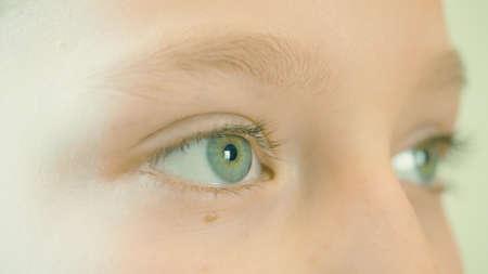 Close up girls eyes. Macro shot shot of girls face with beautiful eyes winking.