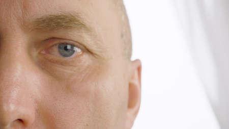 Man eye close up. Macro view mans eye winking. Half of face. Empty copyspace 写真素材