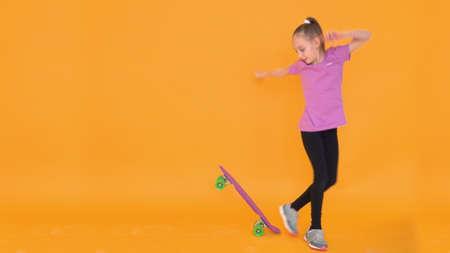 Young teenager girl balancing on skateboard in studio on orange background. Girl skateboarder training on longboard in photo studio. Empty copyspace
