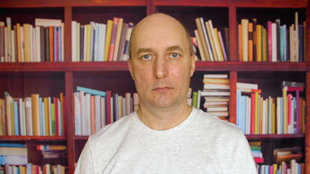 Serious man in the library. Close up view man with a bald head in front of bookshelves in the library. Foto de archivo