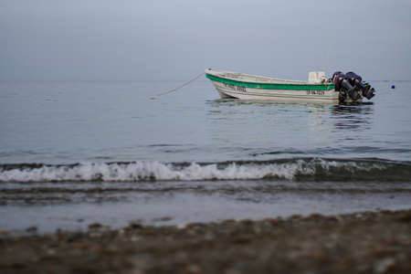 Single boat with green line in the sea seen from the coast
