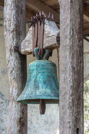 Ancient bronze bell covered with patina hanging from a wooden structure