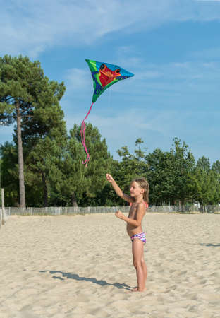 Beautiful little girl on the beach launches a kite at the seashore. Sunshine
