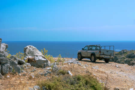 Pickup truck on a mountain road along the sea. Rhodes Greece Europe 免版税图像