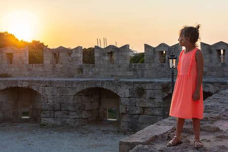 A little girl looks at the setting sun. Mandraki, Old Town, Rhodes