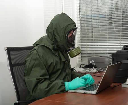 Man in a biohazard protective suit is working on computer