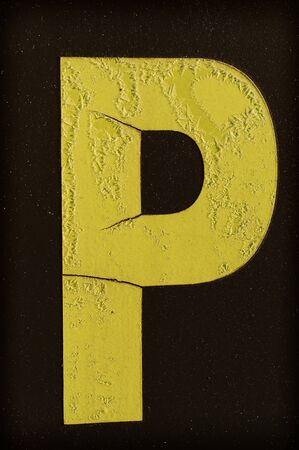 letter word: Yellow letter P covered with frost on black background