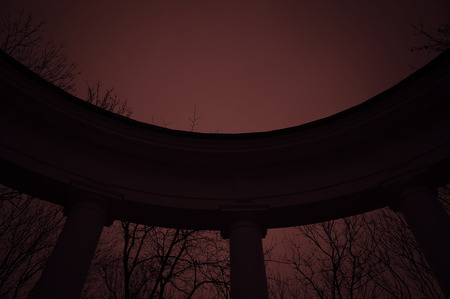 colonnade: Old semicircular colonnade in mystical park in a bloody sunset