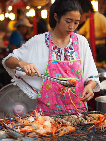 Bangkok, Thailand - August 21, 2016: Woman cooking king prawns and mussels on a barbecue to be sold to customers in Thanon Ratchadamri, Bangkok Editorial