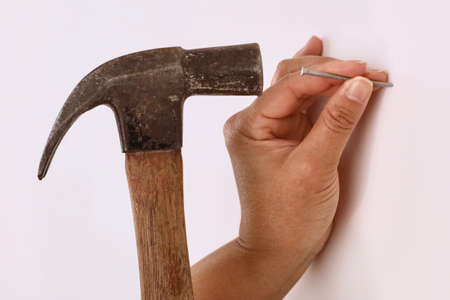 Close-up of a female contractor using a hammer to hammer a nail into a wall Stock Photo