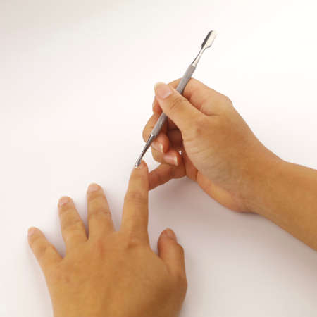 Close-up of a female performing a manicure on herself using a cuticle pusher