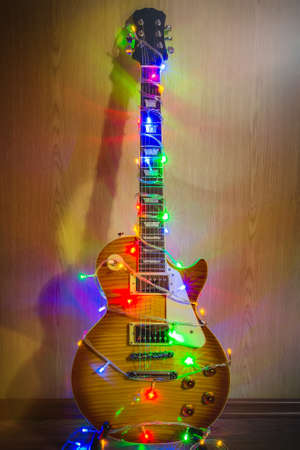 Christmas guitar, guitar dress up in a garland with colored lights close up, new year, music, rock, rock, new year, rock Stock Photo