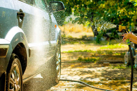 wash the car in the yard with the hose, water sprays