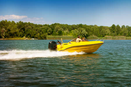 fast yellow motor boat floats on the river