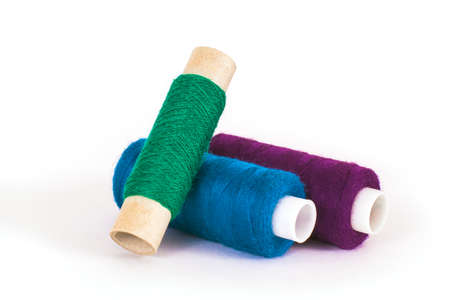 Blue, green and purple sewing threads on white background