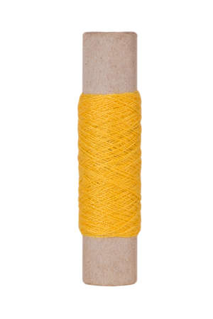 Yellow sewing thread reel on white isolated background