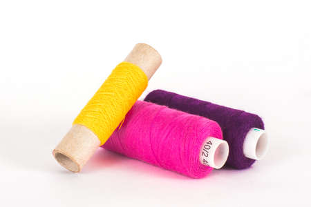 Yellow, pink and purple sewing threads on white background