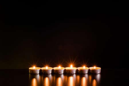Brennende Kerzen auf schwarzem Hintergrund