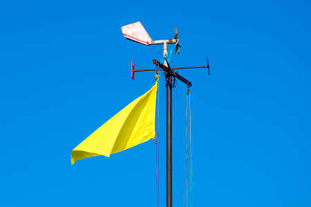 A weather vane and a yellow flag on a background blue sky
