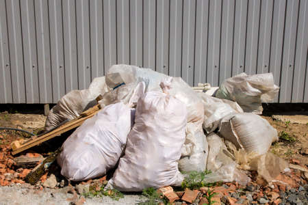 Bags of construction waste lying in a pile in the yard