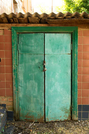 The entrance to the basement is locked. Green old door closed on the padlock.