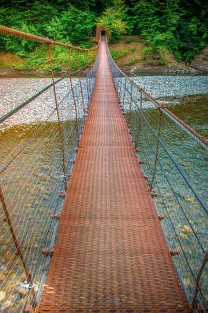 Pedestrian suspension bridge over the Belaya river. Republic Of Adygea, Russia.