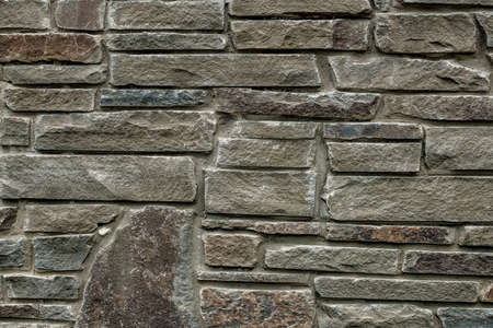 The wall is made of rough natural stone. Gray wall